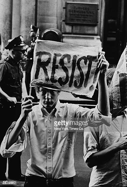 A male demonstrator holds up a 'Resist' banner for the camera at an antiVietnam War rally outside the Whitehall Street military induction center New...