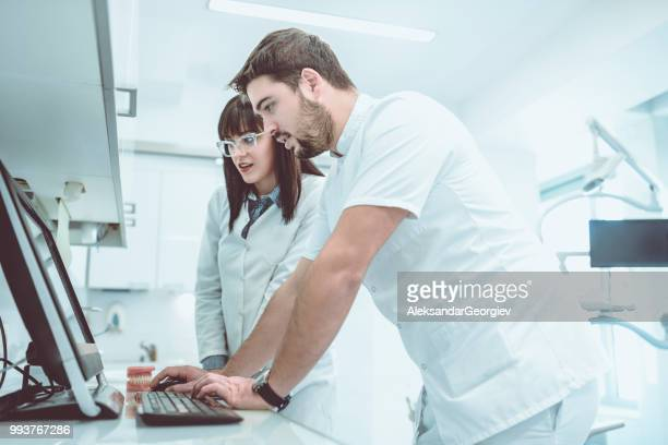 Male Dentist And Assistant Looking At Digital X-Ray Images On Computer