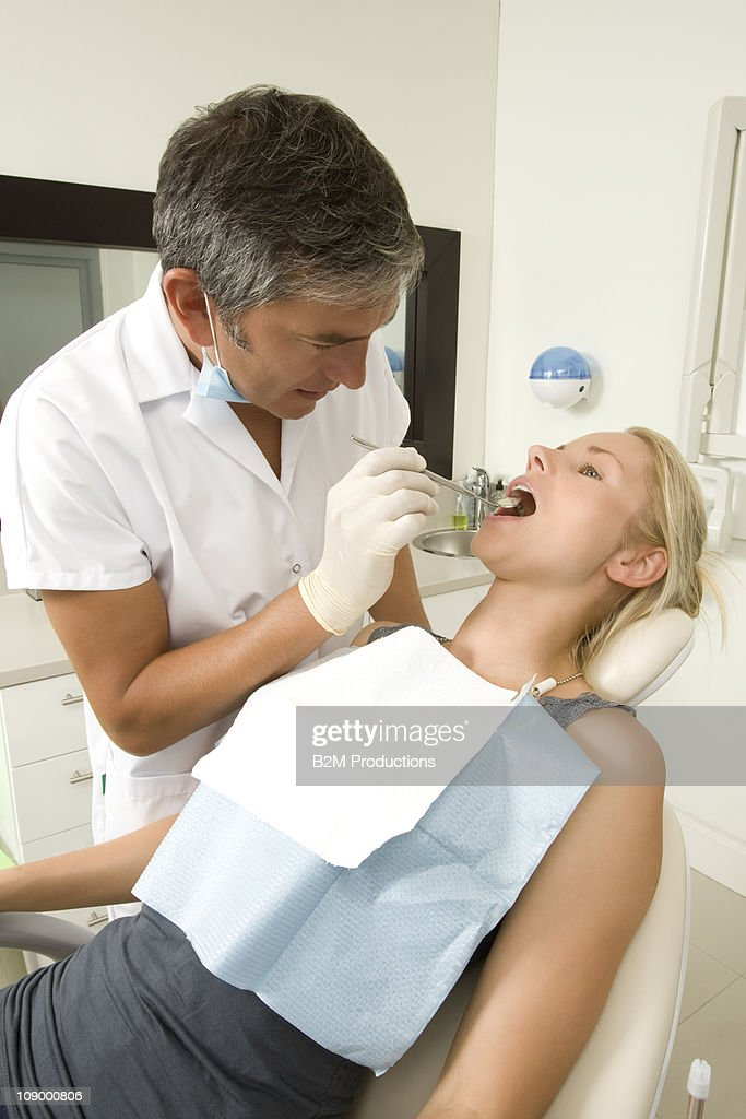 Male dentist examining woman : Stock Photo