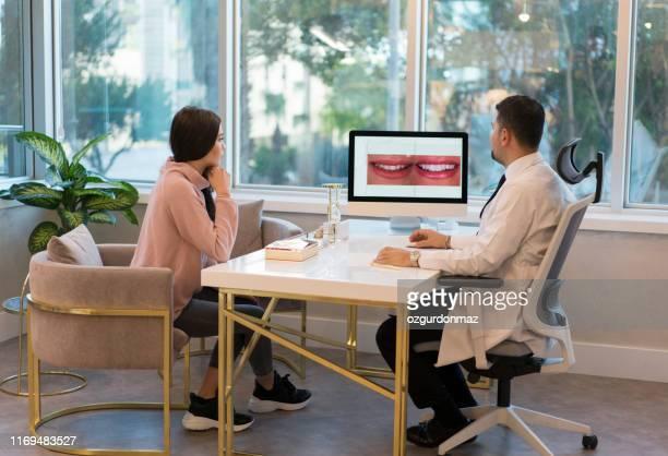 彼女の患者との男性歯科医会議 - 矯正歯科医 ストックフォトと画像