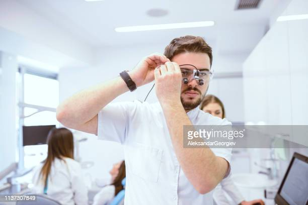 Male Dentist Setting Up Eye Magnifier