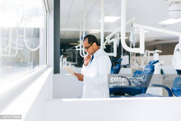 Male dentist standing by window in dental clinic