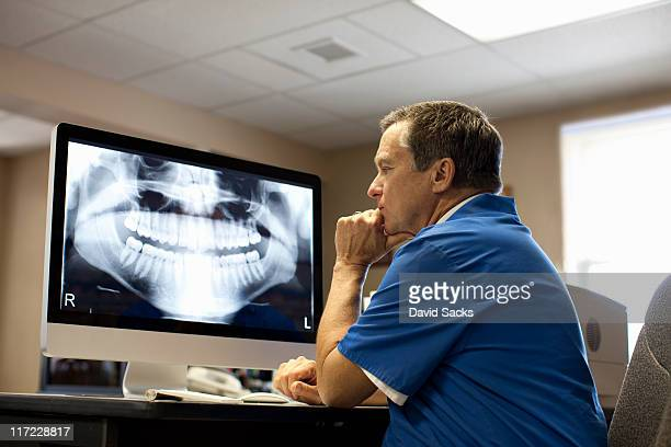Male dentist viewing x-ray on computer screen.