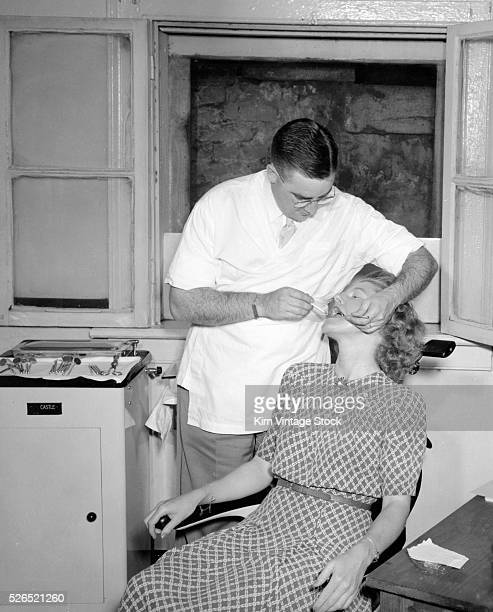 A male dentist works on the mouth of a woman in his dental office in the state of Georgia