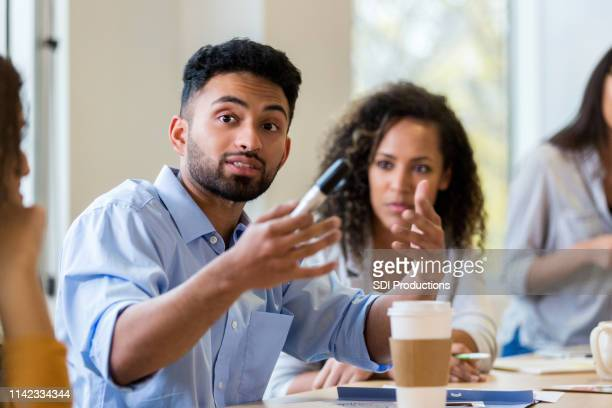 male design professional presents ideas to team - american influenced stock photos and pictures