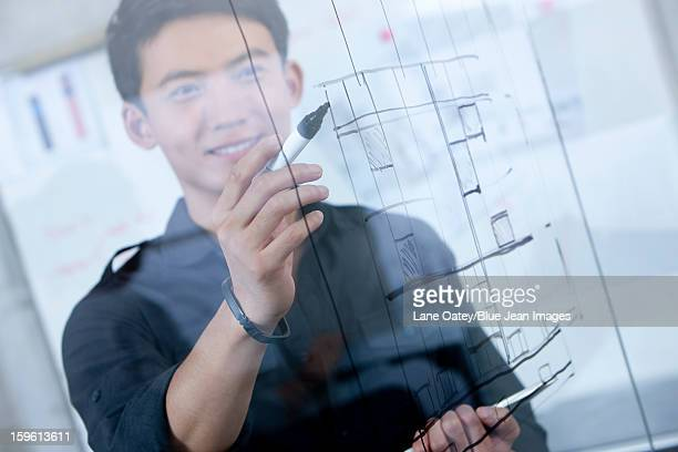 Male designer drawing sketch on glass wall