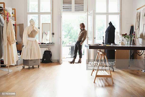 Male designer examining costume on mannequin in studio