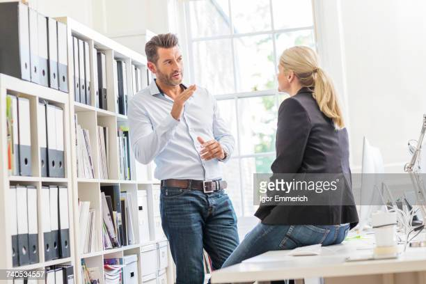 Male designer explaining idea to female colleague in creative studio meeting