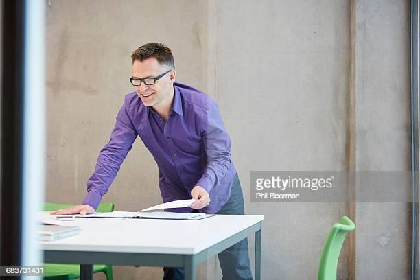 Male designer preparing paperwork in design studio