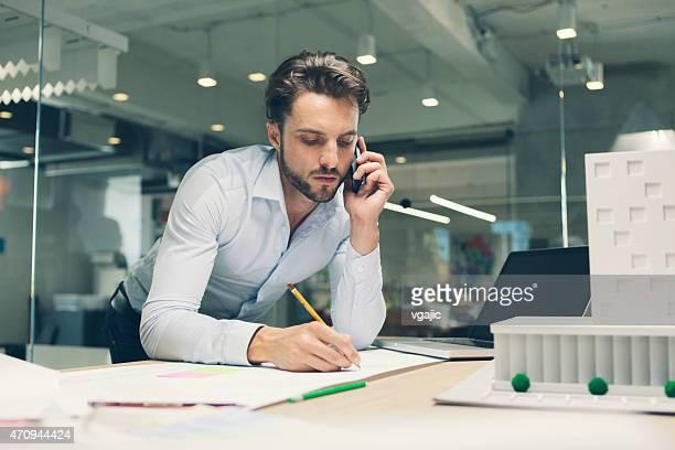 Hombre diseñador hablando por teléfono inteligente en oficina.