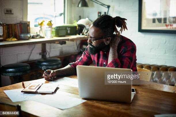male designer with tattoos drawing at desk. - usare il laptop foto e immagini stock