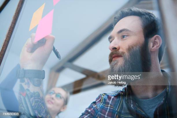 Male designer writing on adhesive note on design studio window