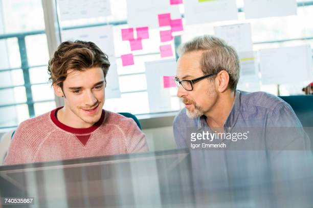 Male digital designer explaining design to trainee at office desk