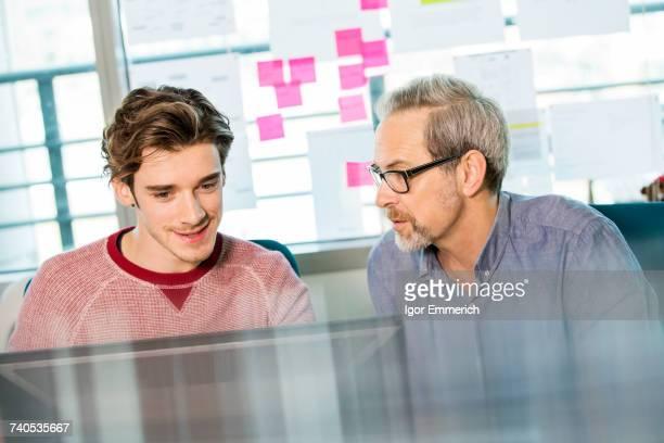Male digital designer explaining design to trainee at office desk
