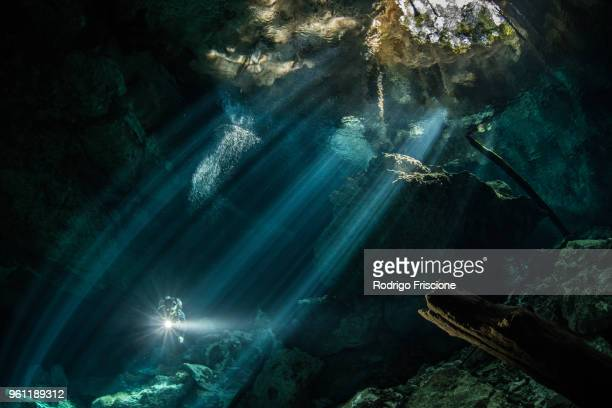male diver diving in underground river (cenote) with sun rays and rock formations, tulum, quintana roo, mexico - 岩層 ストックフォトと画像