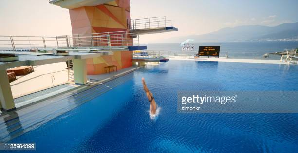 male diver diving into swimming pool - parte inferior imagens e fotografias de stock
