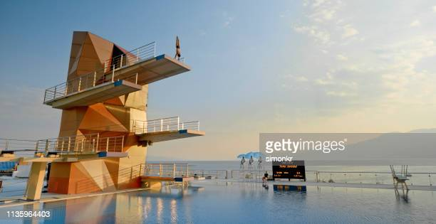 male diver in handstand position on diving board - diving platform stock pictures, royalty-free photos & images