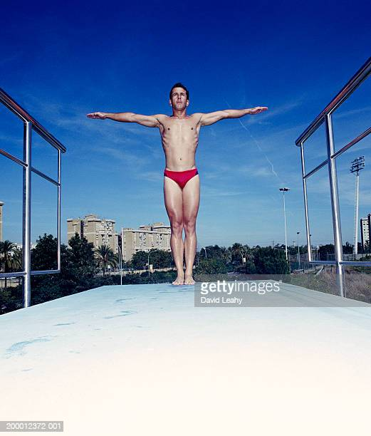 male diver on diving board, arms outstretched - man wearing speedo stock photos and pictures