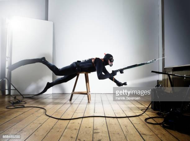 Male diver with speargun in a studio