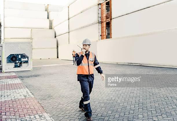 Male dock worker using walkie-talkie in shipyard