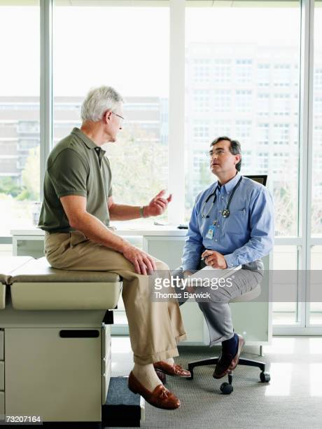 male doctor and patient in exam room - doctor's surgery stock pictures, royalty-free photos & images