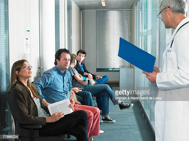 male doctor calling for patients in hospital waiting room. - outpatient care stock pictures, royalty-free photos & images