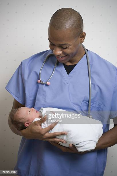 Male doctor carrying a new born baby