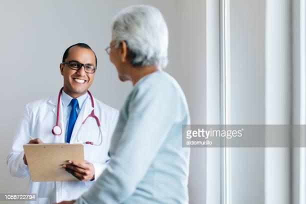 médico masculino verificação paciente do sexo feminino sênior e sorrindo - paciente - fotografias e filmes do acervo