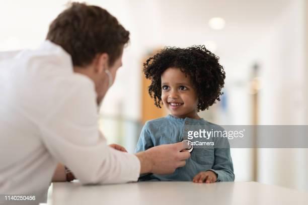 o doutor masculino verific a saúde do coração do seu paciente - pediatra - fotografias e filmes do acervo