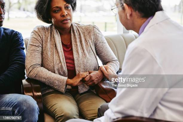 male doctor consoling mature woman sitting with son in hospital lobby - 60 64 years stock pictures, royalty-free photos & images