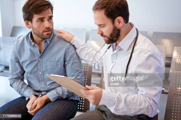 male doctor consoling patient at waiting room - outpatient care stock pictures, royalty-free photos & images