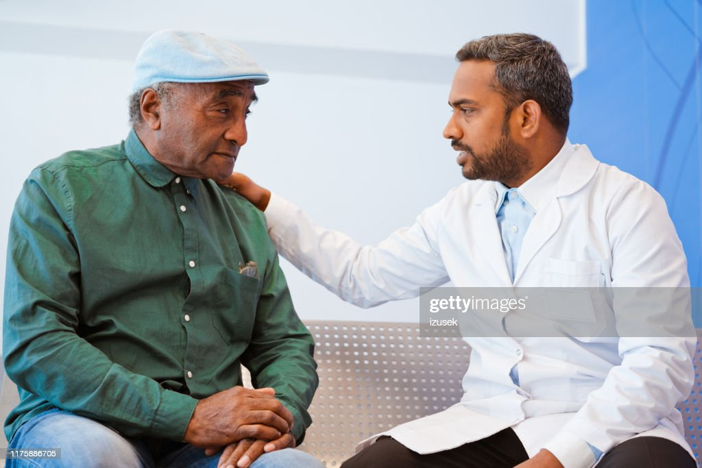 Male doctor consoling senior patient at hospital : Stock Photo
