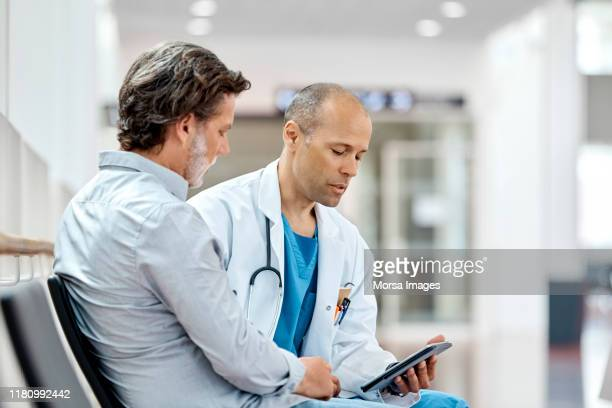 male doctor counseling mature patient at hospital - males stock pictures, royalty-free photos & images