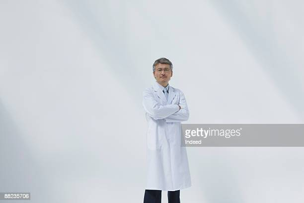 male doctor crossing arms - laborkittel stock-fotos und bilder