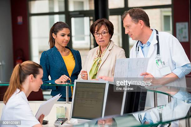 Male doctor discussing report with patients at hospital reception desk
