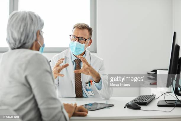 male doctor discussing with woman during covid-19 - doctor stock pictures, royalty-free photos & images