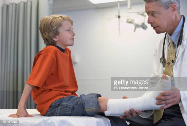 Male doctor examining boy with cast