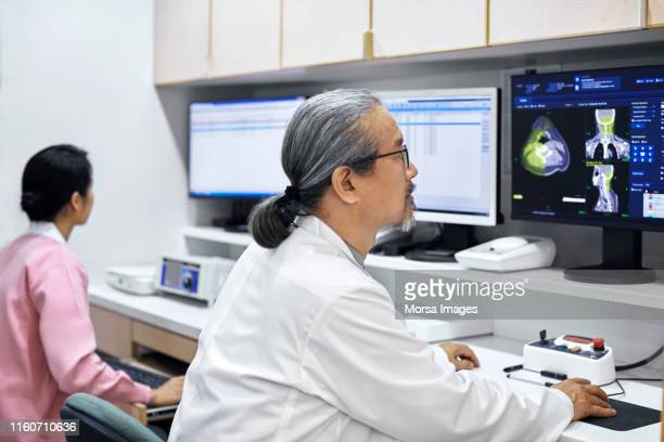 Male doctor examining MRI scans on computer