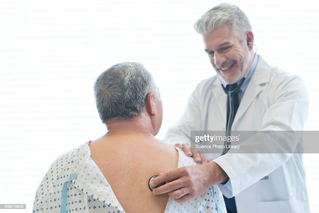 Male Doctor Examining Patient In Hospital Gown Stock Photo | Getty ...