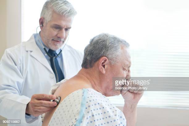 male doctor examining patient in hospital gown - cough stock pictures, royalty-free photos & images