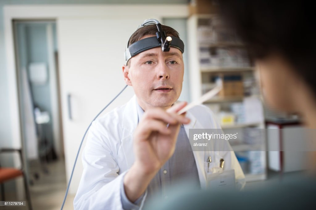 Male doctor examining throat of female patient : Stock Photo