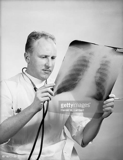 male doctor examining x-ray report - number of people stock pictures, royalty-free photos & images