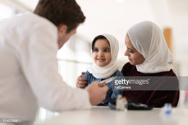 Male doctor explains to a young patient and her mother how to inject insulin
