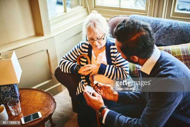 male doctor giving medicines to senior woman - social services stock photos and pictures
