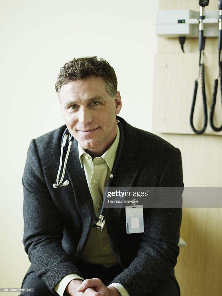 Male doctor in exam room, smiling, portrait, close-up : Stockfoto