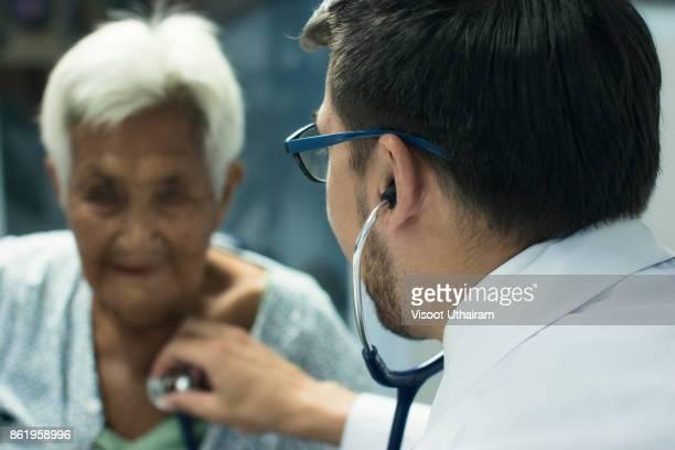 male doctor listening heart beat and breathing of elderly woman - dokterstas stockfoto's en -beelden