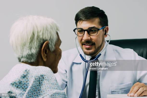 male doctor listening heart beat and breathing of elderly woman. - morbillivirus stock pictures, royalty-free photos & images