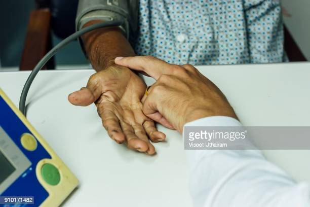 Male Doctor listening heart beat and breathing of Elderly Woman.