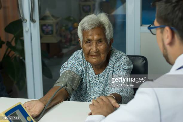 male doctor listening heart beat and breathing of elderly woman - morbillivirus stock pictures, royalty-free photos & images