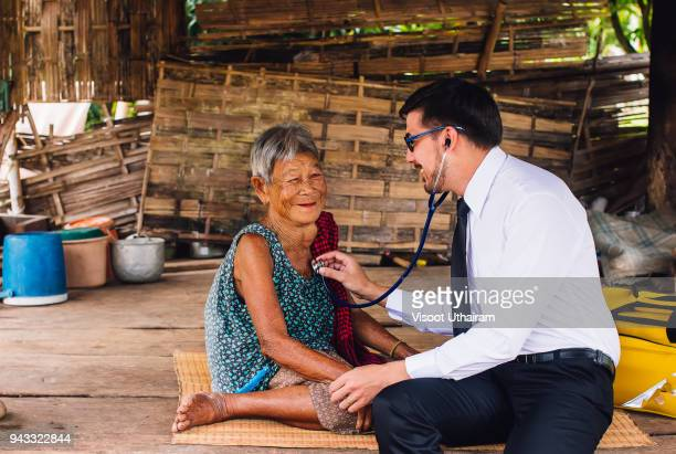 Male Doctor listening heart beat and breathing of Elderly Woman